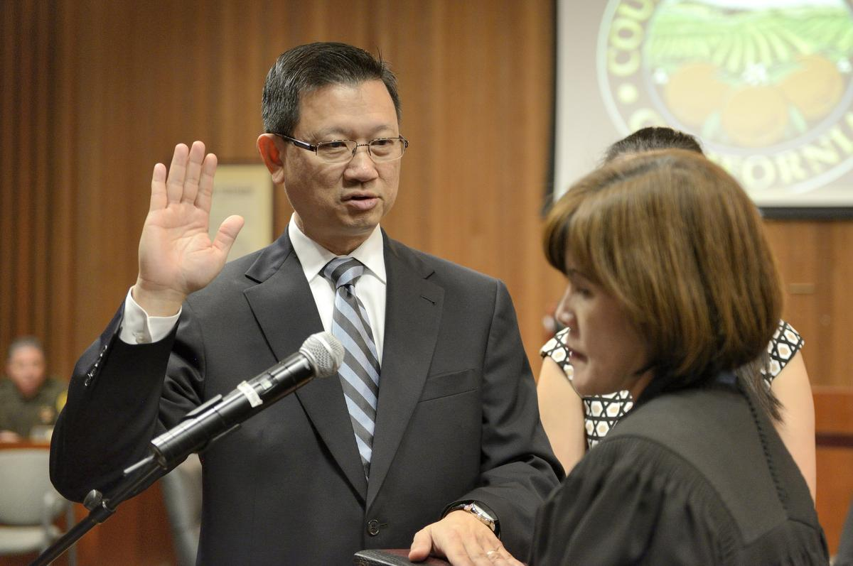 Orange County Supervisor Andrew Do takes the oath of office from his wife, Cheri Pham, as he stands with his daughters, Ilene Do, center, and Rhiannon Do, during the start of the Board of Supervisors meeting on Tuesday in Santa Ana. ///ADDITIONAL INFORMATION: Slug: doswearingin.0204.jag, Day: Tuesday, February 3, 2015 (2/3/15), Time: 9:45:15 AM, Location: Santa Ana, California - Andrew Do - JEFF GRITCHEN, STAFF PHOTOGRAPHER