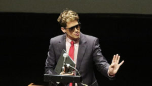 "Milo Yiannopoulos, the polarizing Breitbart News editor, speaks at California Polytechnic State University as part of his ""The Dangerous Faggot Tour"" of college campuses, Tuesday, Jan. 31, 2017, in San Luis Obispo, Calif.  His speech was met with dozens of angry protesters outside a campus theater. (David Middlecamp/The Tribune (of San Luis Obispo) via AP)"