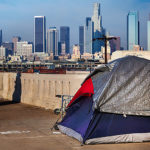 Tent of homeless person on 6th Street Bridge with Los Angeles skyline in the background. California, USA. (Photo By: Education Images/UIG via Getty Images)